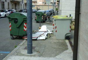 Degrado in città, rete da materasso abbandonata sul marciapiede